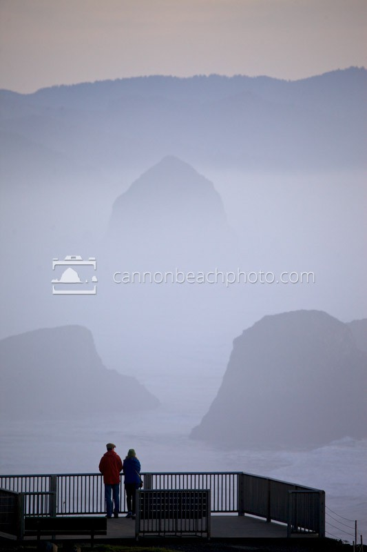 Two tourists look at the misty view of Cannon Beach from Ecola State Park. Simply the best view on the Oregon Coast, even on a foggy day.