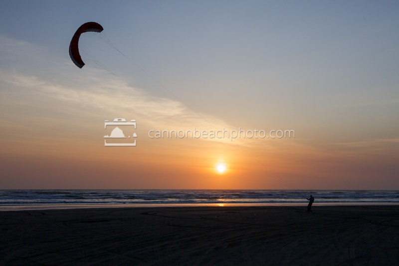 A person kite-boards at sunset on an Oregon Beach. Kite-boarding is a sport the combines being pulled a giant kite and riding on a large skateboard.