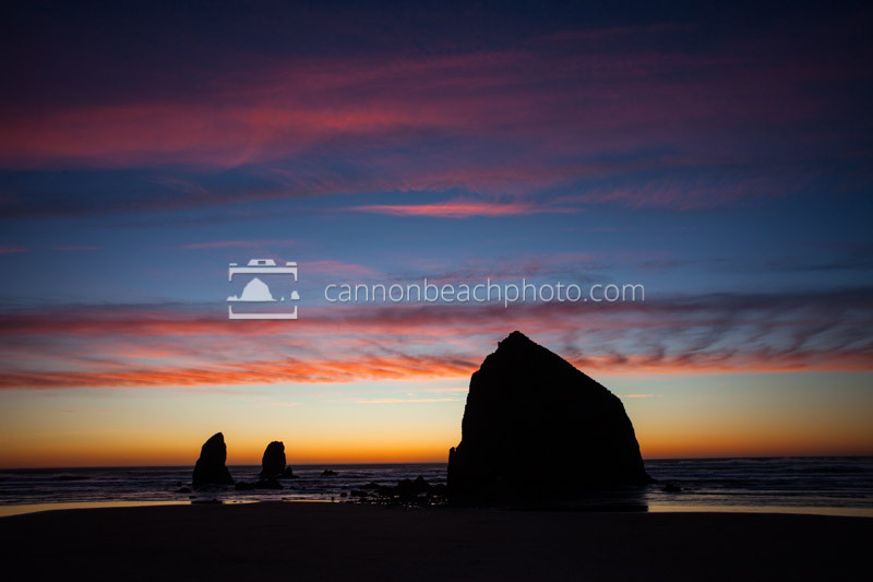 A vibrant winter sunset flares up in the clouds above Haystack Rock in Cannon Beach, Oregon. A beautiful Haystack Rock photo.