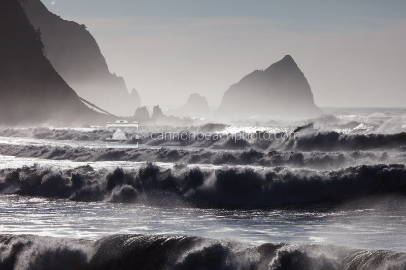 Large waves crash sending spray into the air offshore from Floatilla Beach below Tillamook Head.