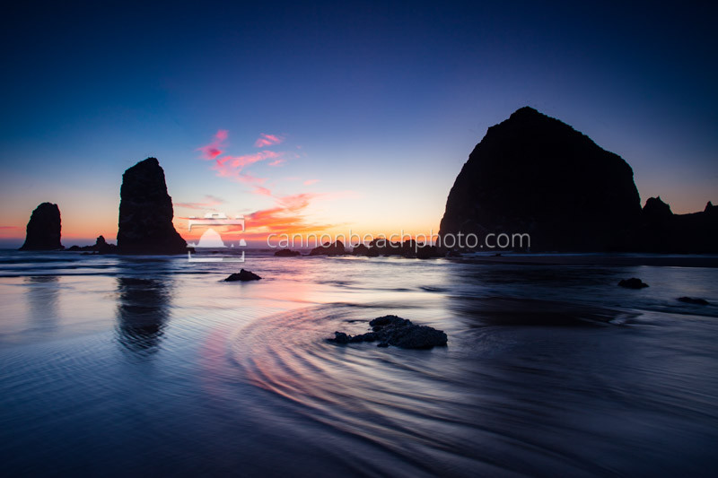 The waves rebound around the rocks during the last glimpse of color at Haystack Rock.