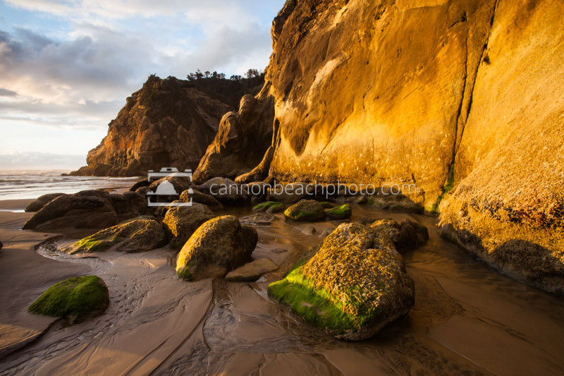 Sunlight glints off the sandstone rocks of Hug Point. During the early 1900s, stagecoaches and automobiles drove around the rock ledge of Hug Point at low tide to travel north or south on the coastline.