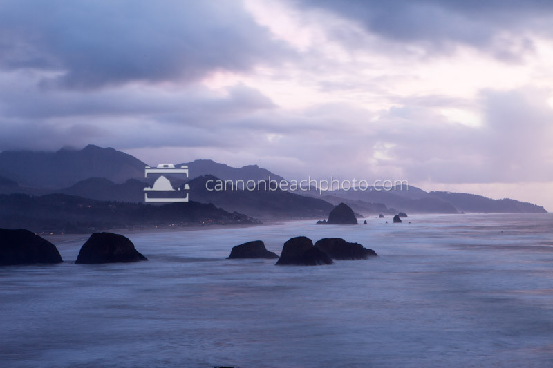 Both clouds and waves roll through this slow exposure image of Cannon Beach from the famous Ecola State Park viewpoint on the Oregon Coast. A moody cloudy evening seascape.