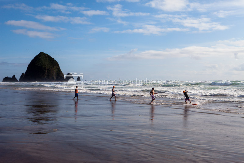 People Skimboarding and Playing in the Surf