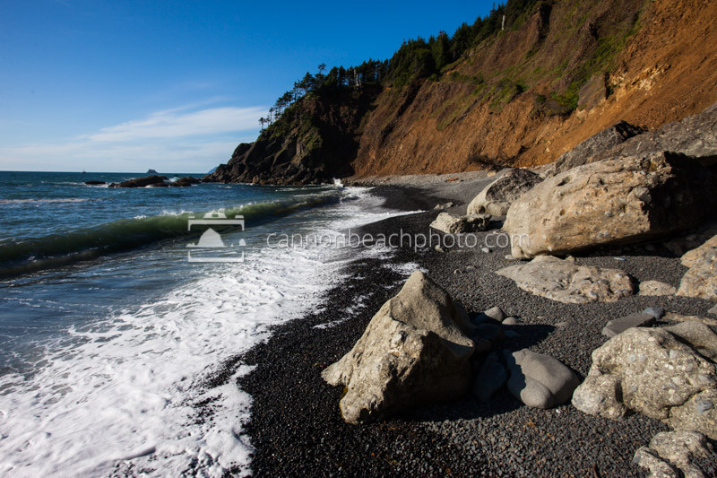 A Wave Crests Unto The Black Stones Of Secret Beach Along Oregon Coast