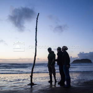 Three People Observe Beach Art
