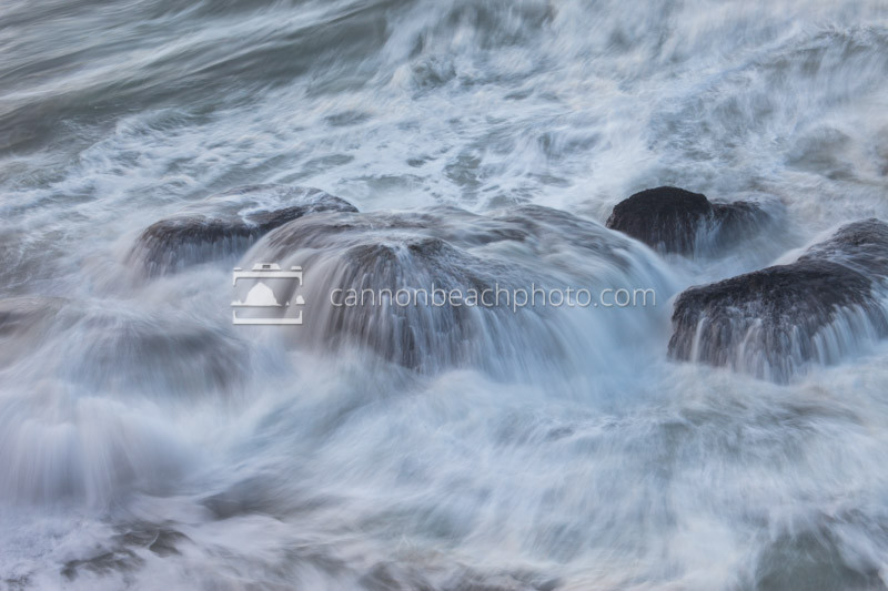 Waves cascade off the immersed sea-boulders making the water look like strands of hair. A joyful and beautiful movement of wave water near Falcon Cove, Oregon.