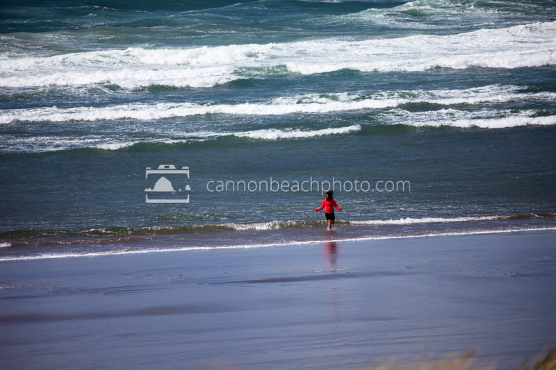 Lady in a Red Jacket Plays in the Surf