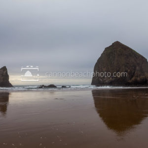 Winter Haystack Rock with Cloudy Skies