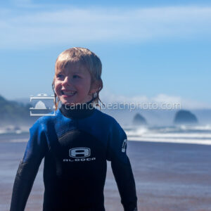 Kid in Wetsuit Grinning on the Beach