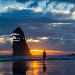 Silhouetted Woman at Sunset with Needle Seastack