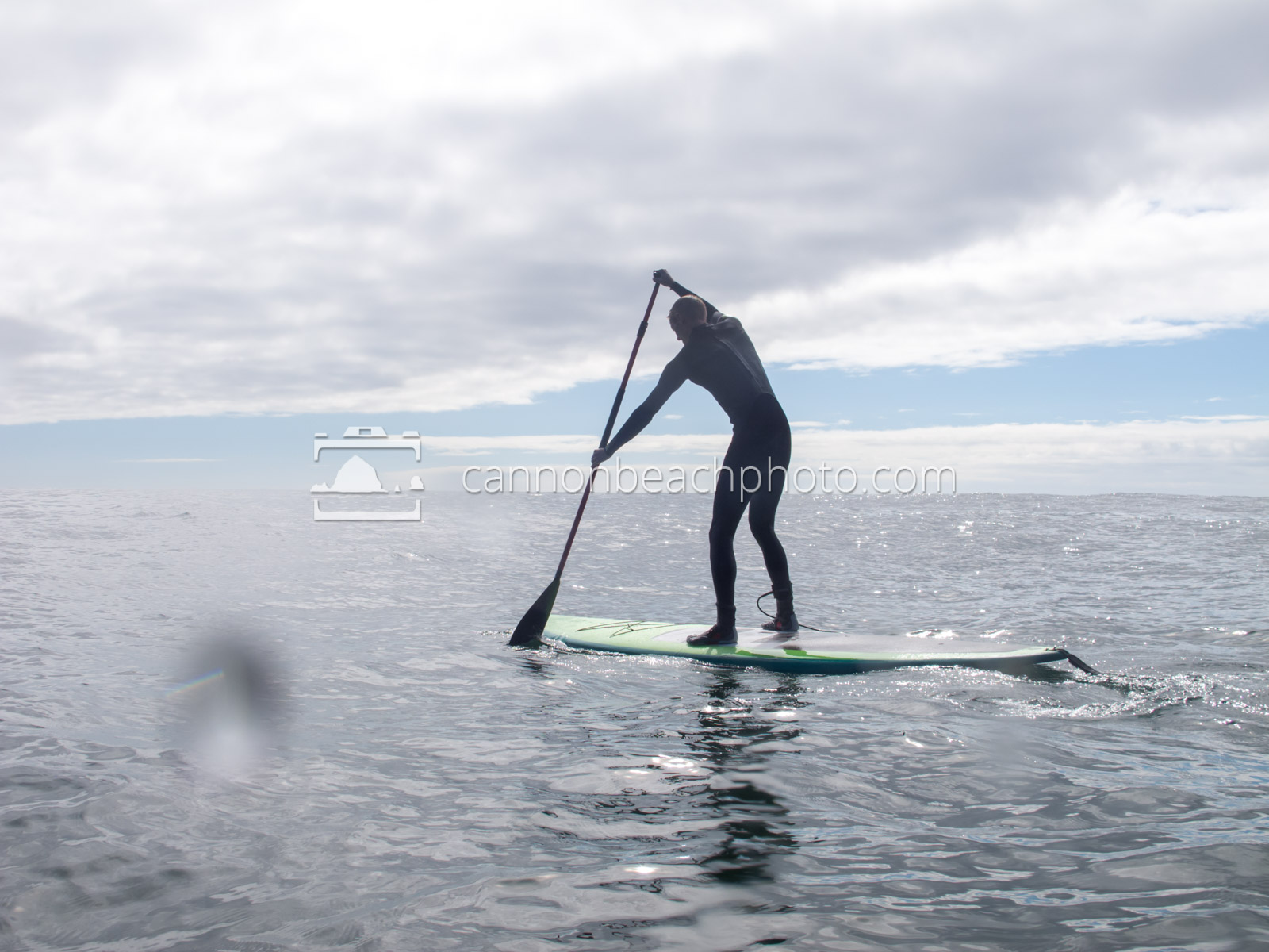 Young Man Paddleboarding on the Pacific Ocean